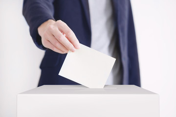 vote image, a person about to place ballot in a box